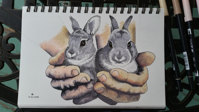 A pair of hands cups a pair of grey bunnies.