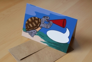 A photo of a notecard picturing a tortoise with a bullhorn and a blank speech bubble. You can write your own message in the speech bubble!