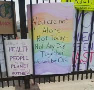 "The most prominent sign reads ""You are not Alone/not Today - Not Any Day/Together/We will be OK"""