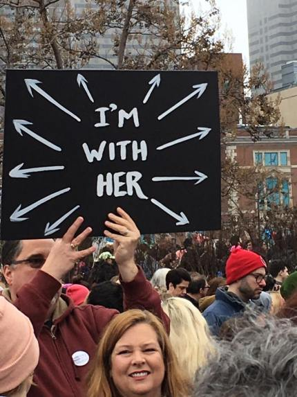 "A man holds a sign that reads ""I'm with her"" and arrows pointing in all directions at the surrounding crowd. Photo by Jayne Selwa."