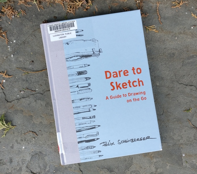 IMAGE #2 DESCRIPTION: A photo of the book Dare to Sketch by Felix Scheinberger. The book is a library book with a blue cover, with loose black line drawings of pens, pencils, and a pencil case vertically along the left side of the book. The book is photographed against a stone background with some plant detritus here and there.